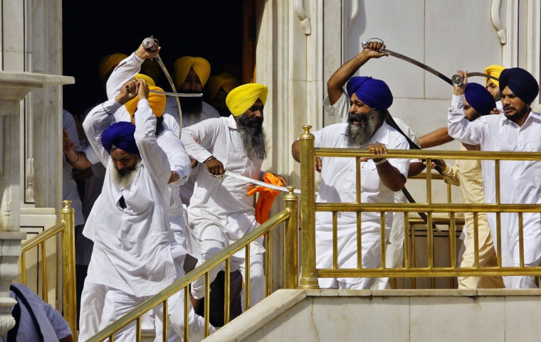 Sikhs wield swords during their clash inside the complex of the holy Sikh shrine, the Golden Temple, in the northern Indian city of Amritsar June 6, 2014. Sikhs wielding swords clashed inside the compound of their religion's holiest shrine on Friday, the 30th anniversary of a controversial raid by Indian security forces that flushed out separatist militants holed up in the temple. (Munish Sharma/Reuters)