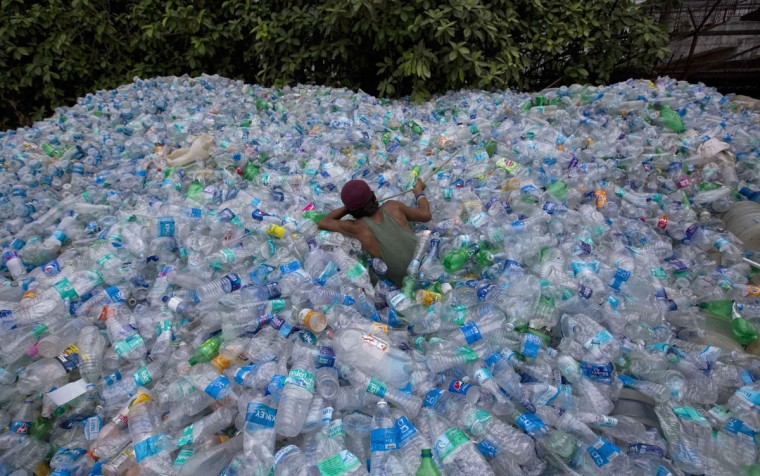 A worker uses a rope to move through a pile of empty plastic bottles at a recycling workshop in Mumbai June 5, 2014. According to the United Nations Environment Programme website, World Environment Day is celebrated annually on June 5 to raise global awareness and motivate action for environmental protection. (Danish Siddiqui/Reuters)