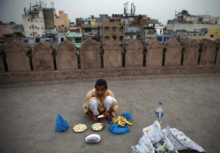 A Muslim boy cuts a banana into pieces before the Iftar (breaking of fast) meal on the first day of the holy month of Ramadan in India, at the Jama Masjid (Grand Mosque) in the old quarters of Delhi June 30, 2014. (Ahmad Masood/Reuters)