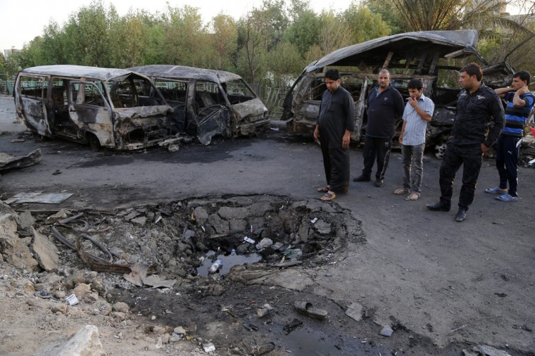 People gather at the site of a car bomb attack in Baghdad's Sadr City, June 18, 2014. At least 13 people were killed and 30 others wounded in a car bomb explosion in Baghdad's mainly Shi'ite neighborhood of Sadr City, according to police and hospital officials. (Wissm al-Okili/Reuters)
