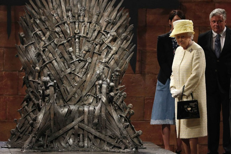 Britain's Queen Elizabeth looks at the Iron Throne as she meets members of the cast on the set of the television show Game of Thrones in the Titanic Quarter of Belfast, Northern Ireland, June 24, 2014. (REUTERS/Phil Noble)