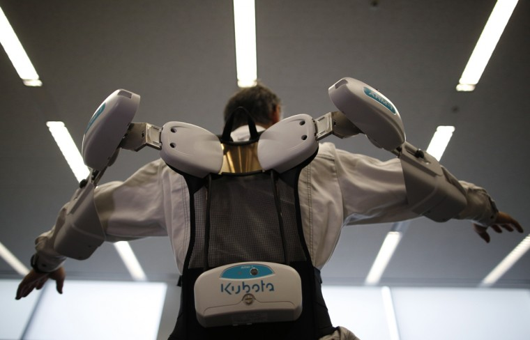 An employee of ActiveLink Co. established under the intrapreneurship of Panasonic Corp, demonstrates ARM01, called 'Raku Vest', jointly developed with Kubota Corp., in Tokyo June 2, 2014. The ARM01is a robotic exoskeleton developed to help farmers and construction workers. (Issei Kato/Reuters)
