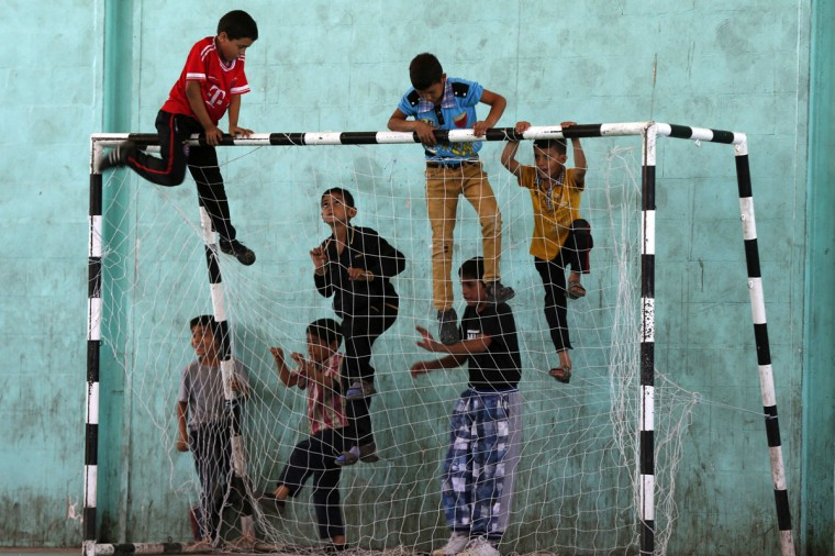 Syrian and Palestinian refugee children climb up a goalpost before the start of a soccer match in the Al-Baqaa Palestinian refugee camp, near Amman June 17, 2014. The football league between young Syrian and Palestinian refugees and Jordanian youth is organized by Oxfam and the al-Baqaa youth club to commemorate World Refugee Day, which falls on June 20. The matches aim to foster positive relationships between communities, fighting exclusion and marginalization, while promoting trust and friendship, according to the organiser. (REUTERS/Muhammad Hamed)