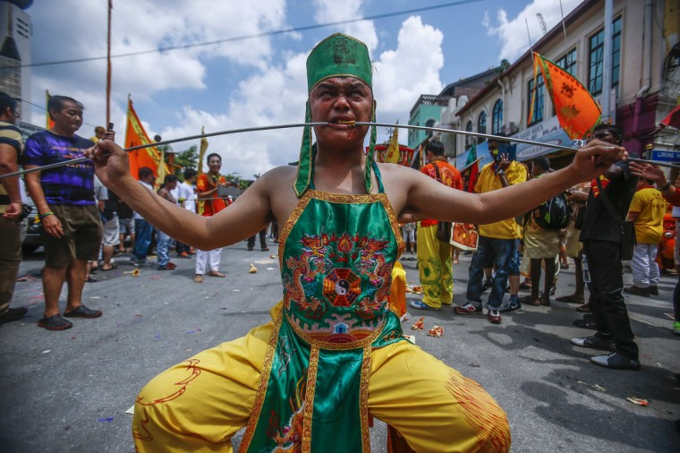 A Chinese devotee who has his cheeks pierced with a skewer sits on a chair before marching around Chinatown during the Guan Ping Festival in Kuala Lumpur June 8, 2014. The festival, held in celebration to mark the birthday of Chinese deity Guan Ping, is believed to bring prosperity for local businesses. (Samsul Said/Reuters)