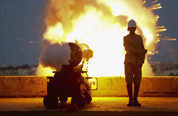 A National Heritage Trust historical re-enactor in Victorian-era Royal Malta Artillery uniform fires one of several cannons during an activity to mark the feast day of Saint John the Baptist, patron saint of the Knights of the Order of Saint John, on the bastions of Valletta. The Order ruled Malta between 1530 and 1798. (Darrin Zammit Lupi/Reuters photo)