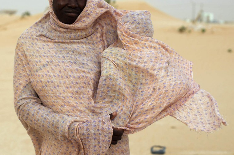 A woman shields her child from the wind while walking on sand dunes in Nouakchott . (Joe Penney/Reuters photo)
