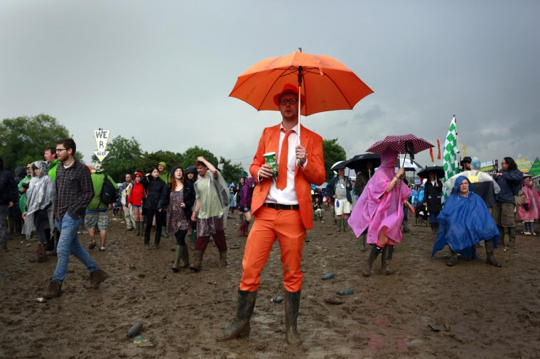 A man dressed in an orange suit watches Robert Plant on the Pyramid stage at Worthy Farm in Somerset, during the Glastonbury Festival June 28, 2014. (Cathal McNaughton/Reuters)