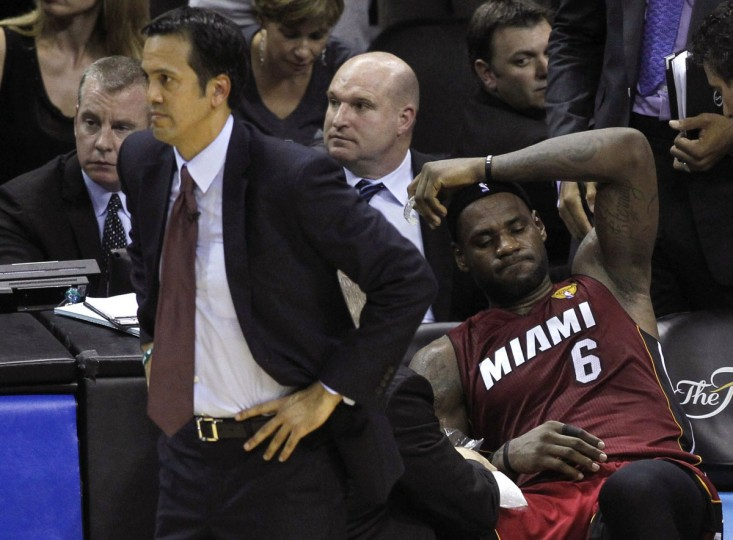 Miami Heat's LeBron James (R) sits on the bench after hurting his leg as coach Erik Spoelstra watches the game during the fourth quarter against the San Antonio Spurs in Game 1 of their NBA Finals basketball series in San Antonio, Texas June 5, 2014. (Mike Stone/Reuters)