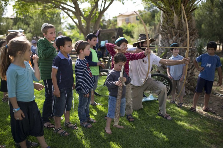 Children learn how to shoot a bow and arrow during an event marking the holiday of Lag Ba'Omer in the West Bank Jewish settlement of Maon, south of Hebron May 19, 2014. Israeli lawmakers are pressing Prime Minister Benjamin Netanyahu to lift what they call unjustified secrecy over opaque - and rising - funding for settlements on West Bank land Palestinians want for a state. Picture taken May 19, 2014. (REUTERS/Amir Cohen)