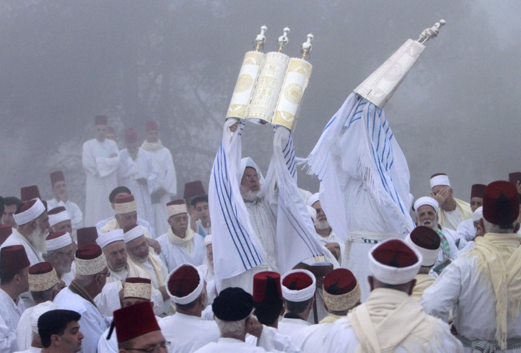 Members of the Samaritan hold up Torah scrolls during a traditional pilgrimage marking the holiday of Shavuot, atop Mount Gerizim near the West Bank city of Nablus early June 8, 2014. The Samaritans, who trace their roots to the biblical Kingdom of Israel in what is now the northern occupied West Bank, observe religious practices similar to those of Judaism. (Abed Omar Qusini/Reuters)