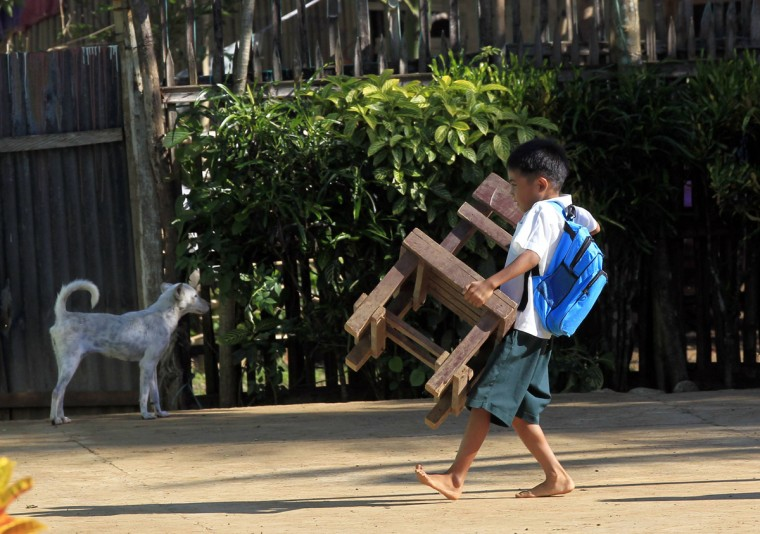 A boy carries a chair towards a classroom on the first day of the new school year at Casili Elementary School in Rodriguez, Rizal province, east of Manila June 2, 2014. Around 23 million students were present for the opening of the new school year in the Philippines, the Department of Education reported on Monday. (Romeo Ranoco/Reuters)