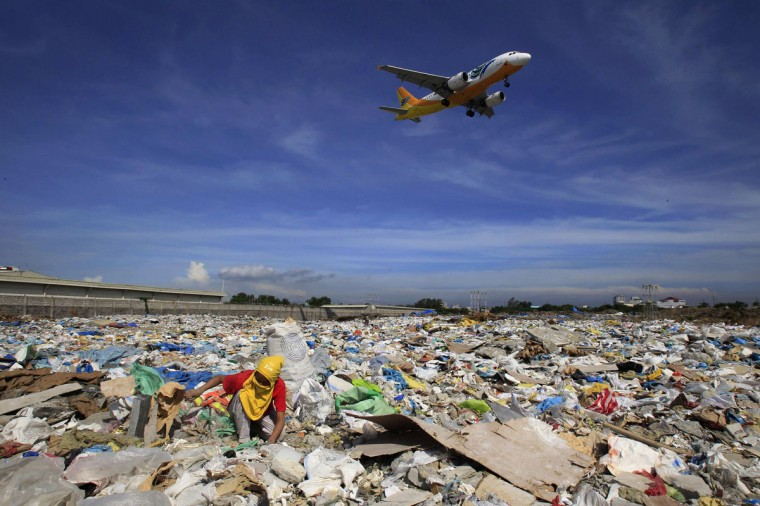 "An aircraft flies overhead as a person rummages for recyclables at a garbage dumpsite in Paranaque city, metro Manila June 8, 2014. The United Nations declared ""Small Islands and Climate Change"" the theme of 2014 World Environment Day, with the year's official 2014 slogan being ""Raise your voice, not the sea level"". (Romeo Ranoco/Reuters)"