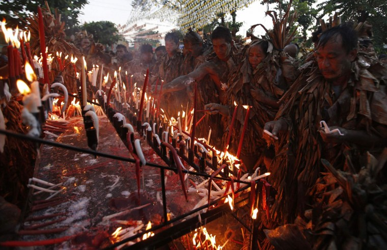 "Residents, covered with dried banana leaves and mud, light candles as they take part in a religious ritual known locally as ""Taong Putik"" (Mud People), while celebrating the Catholic feast day of Saint John the Baptist in the village of Bibiclat, Nueva Ecija, north of Manila, June 24, 2014. According to Saint John the Baptist parish church, hundreds of devotees participated in this year's feast day, which has been observed in the village since 1945, to seek blessings and bountiful harvests. (REUTERS/Erik De Castro)"
