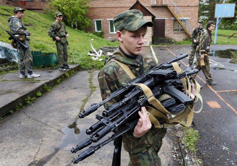 A student of the Scorpion Youth Military Club carries AK-74 Kalashnikov automatic rifles for a training session on a summer base in a school in the village of Molodyozhny, outside Russia's Siberian city of Krasnoyarsk. (Ilya Naymushin/Reuters)