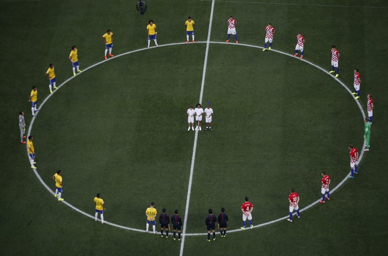 Brazil and Croatia players stand in a circle as doves (C) are released before kickoff at the 2014 World Cup opening match at the Corinthians arena in Sao Paulo June 12, 2014. (Fabrizio Bensch/Reuters)