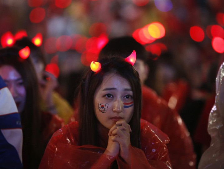 A South Korean fan watches a live TV broadcast of her team's 2014 World Cup Group H soccer match against Algeria, in Seoul June 23, 2014. Algeria opened the goal scoring floodgates swamping South Korea 4-2 in a thrilling World Cup Group H clash on Sunday that kept hopes of securing a spot in the last 16 alive and triggered celebrations across the Arab nation. (Kim Hong-Ji/Reuters)