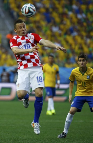 Brazil's Oscar watches as Croatia's Ivica Olic heads the ball during their 2014 World Cup opening match at the Corinthians arena in Sao Paulo June 12, 2014. (Kai Pfaffenbach/Reuters)