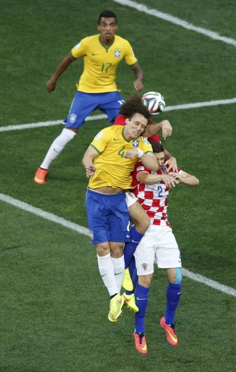 Brazil's David Luiz (front) jumps for the ball with Croatia's Vedran Corluka (obscured) and Sime Vrsaljko (R) during the 2014 World Cup opening match at the Corinthians arena in Sao Paulo June 12, 2014. (Paulo Whitaker/Reuters)