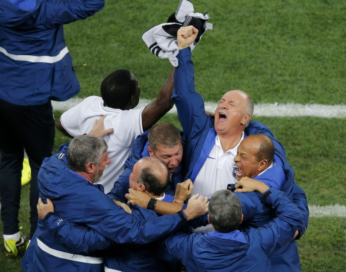 Brazil's coach Luiz Felipe Scolari (top, R) celebrates after Neymar scored a goal during the 2014 World Cup opening match at the Corinthians arena in Sao Paulo June 12, 2014. (Paulo Whitaker/Reuters)