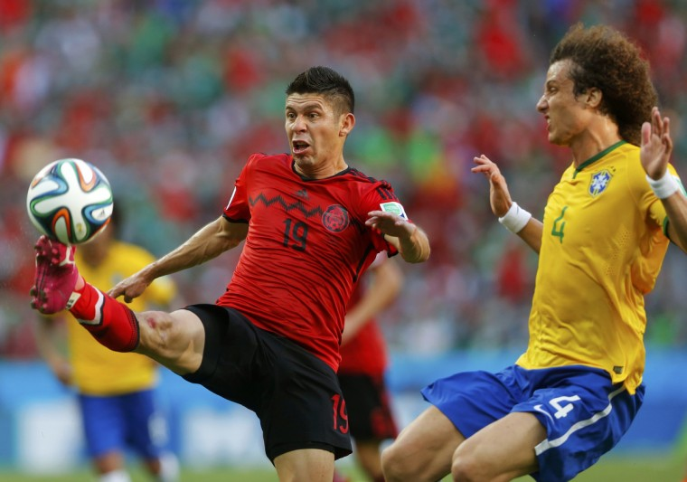 Mexico's Oribe Peralta (L) fights for the ball with Brazil's David Luiz during their 2014 World Cup Group A soccer match at the Castelao arena in Fortaleza June 17, 2014. (Laszlo Balogh/Reuters)