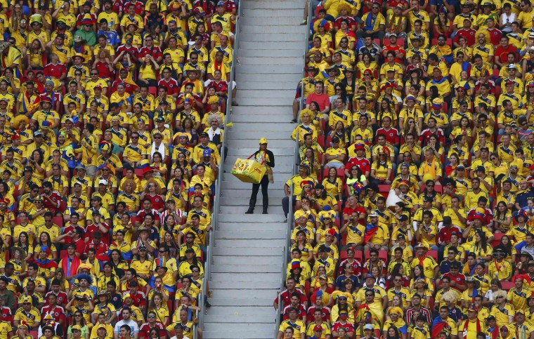 A vendor walks down the stairs as fans watch the 2014 World Cup Group C soccer match between Ivory Coast and Colombia at the Brasilia national stadium in Brasilia June 19, 2014. (Eddie Keogh/Reuters)