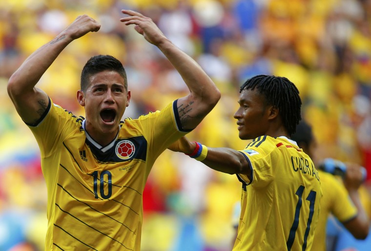 Colombia's James Rodriguez (L) celebrates next to teammate Juan Cuadrado scoring against Ivory Coast during their 2014 World Cup Group C soccer match at the Brasilia national stadium in Brasilia June 19, 2014. (Paul Hanna/Reuters)