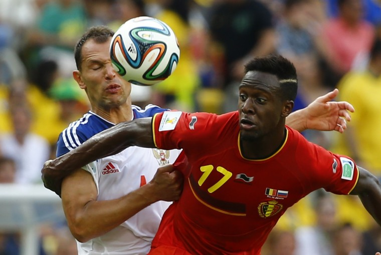 Russia's Sergey Ignashevich (L) fights for the ball with Belgium's Divock Origi during their 2014 World Cup Group H soccer match at the Maracana stadium in Rio de Janeiro June 22, 2014. (Pilar Olivares/Reuters)