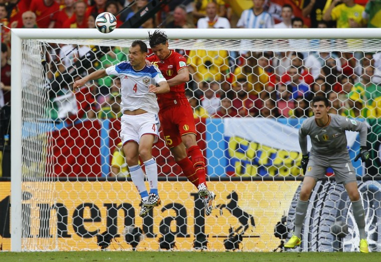 Russia's Sergey Ignashevich (4) jumps for the ball with Belgium's Daniel Van Buyten during their 2014 World Cup Group H soccer match at the Maracana stadium in Rio de Janeiro June 22, 2014. (Pilar Olivares/Reuters)