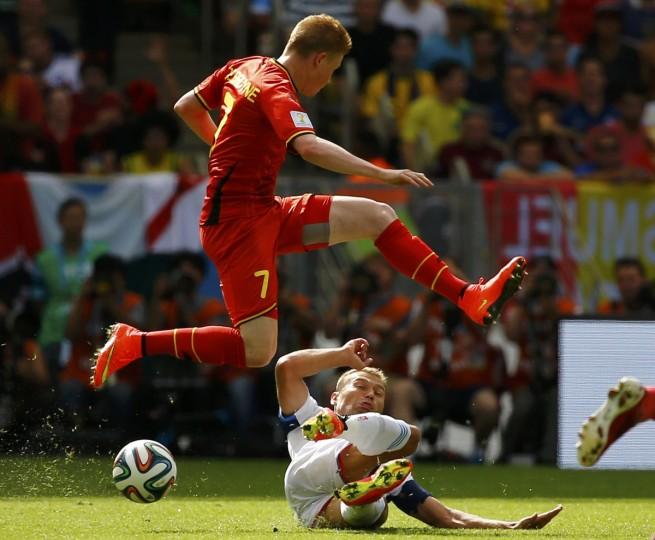 Belgium's Kevin De Bruyne (L) leaps over Russia's Vasili Berezutskiy during their 2014 World Cup Group H soccer match at the Maracana stadium in Rio de Janeiro June 22, 2014. (Pilar Olivares/Reuters)
