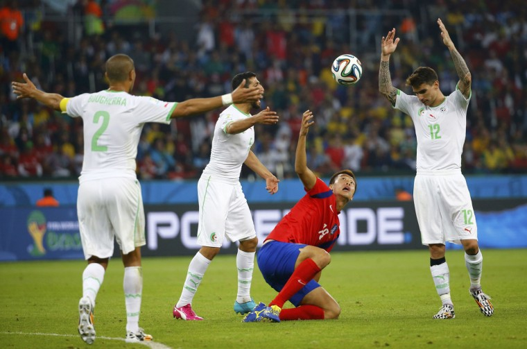 Algeria's Madjid Bougherra (L), Rafik Halliche and Carl Medjani (R) react after Medjani pulled South Korea's Kim Shin-wook (C) down during their 2014 World Cup Group H soccer match at the Beira Rio stadium in Porto Alegre June 22, 2014. South Korea was awarded a free kick. (Murad Sezer/Reuters)