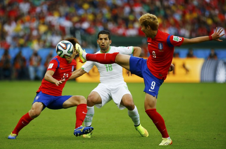 Algeria's Abdelmoumene Djabou (C) fights for the ball with South Korea's Lee Yong (L) and Son Heung-min during their 2014 World Cup Group H soccer match at the Beira Rio stadium in Porto Alegre June 22, 2014. (Damir Sagolj/Reuters)