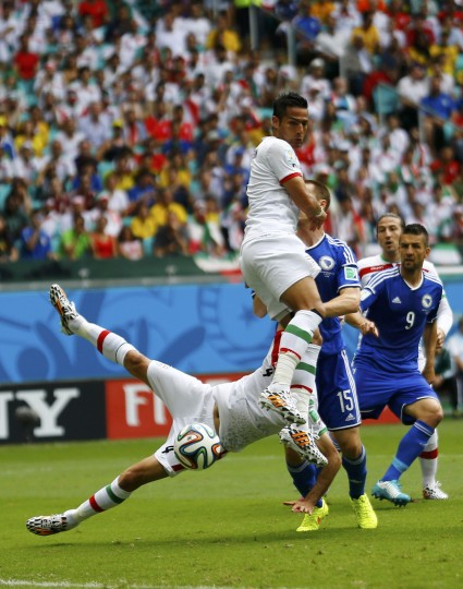 Iran's Jalal Hosseini falls near teammate Amir-Hossein Sadeghi while being challenged by Bosnia's Toni Sunjic (3rd R) during their 2014 World Cup Group F soccer match at the Fonte Nova arena in Salvador June 25, 2014. (Ivan Alvarado/Reuters)