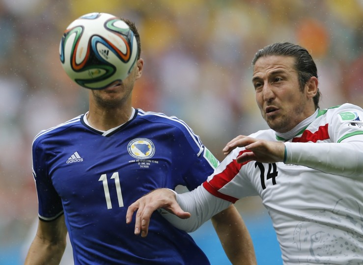 Bosnia's Edin Dzeko (L) fights for the ball with Iran's Andranik Teymourian during their 2014 World Cup Group F soccer match at the Fonte Nova arena in Salvador June 25, 2014. (Sergio Perez/Reuters)