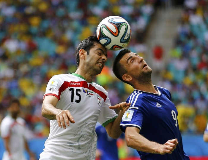 Iran's Pejman Montazeri (L) jumps for the ball with Bosnia's Vedad Ibisevic during their 2014 World Cup Group F soccer match at the Fonte Nova arena in Salvador June 25, 2014. (Ivan Alvarado/Reuters)