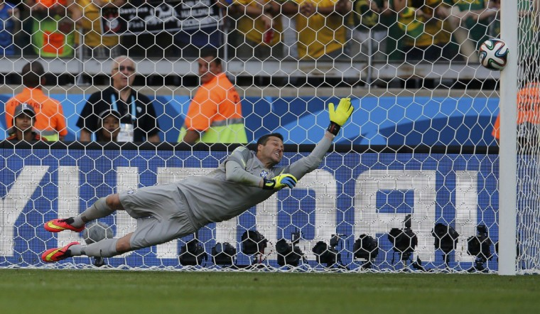 Brazil's Julio Cesar dives as the ball shot by Chile's Gonzalo Jara (unseen) rebounds off the post to decide their penalty shootout in their 2014 World Cup round of 16 game at the Mineirao stadium in Belo Horizonte June 28, 2014. (Sergio Perez/Reuters)