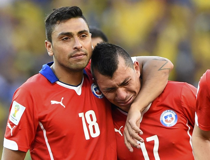 Chile's Gonzalo Jara (L) comforts his teammate Gary Medel after losing their 2014 World Cup round of 16 game against Brazil at the Mineirao stadium in Belo Horizonte June 28, 2014. (Dylan Martinez/Reuters)
