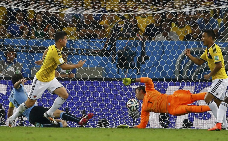 Colombia's James Rodriguez (2nd R) shoots to score his second goal for the team past Uruguay's goalkeeper Fernando Muslera during their 2014 World Cup round of 16 game at the Maracana stadium in Rio de Janeiro June 28, 2014. (Pilar Olivares/Reuters)