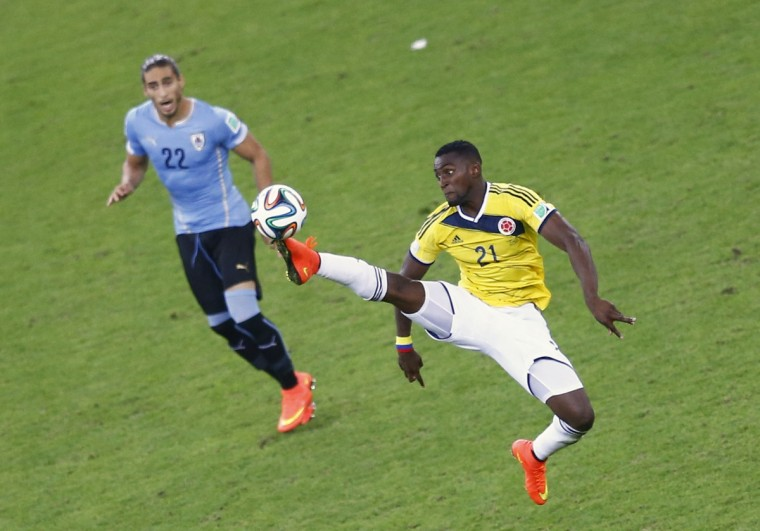 Colombia's Jackson Martinez jumps for the ball as Uruguay's Martin Caceres looks on during their 2014 World Cup round of 16 game at the Maracana stadium in Rio de Janeiro June 28, 2014. (Ricardo Moraes/Reuters)
