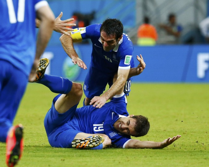 Greece's Sokratis Papastathopoulos (bottom) celebrates after scoring a goal with teammate Giorgos Karagounis during their 2014 World Cup round of 16 game against Costa Rica at the Pernambuco arena in Recife June 29, 2014. (Tony Gentile/Reuters)