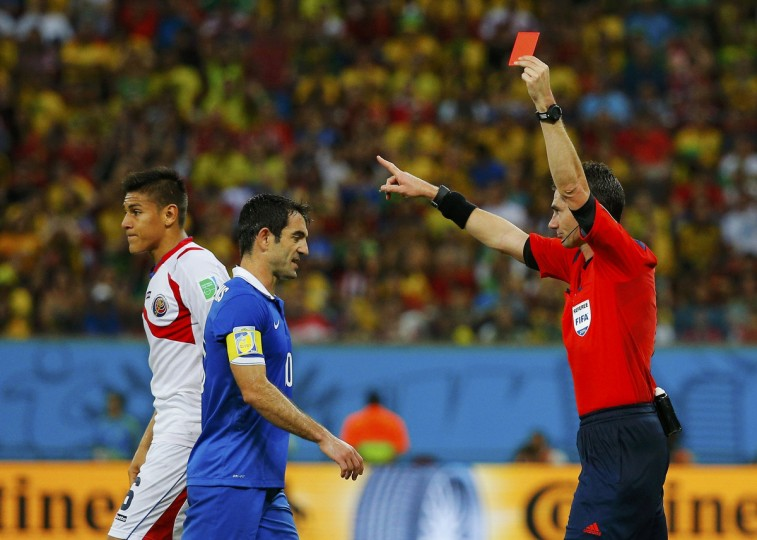 Costa Rica's Oscar Duarte (L) walks off the pitch past Greece's Giorgos Karagounis after being shown the red card by referee Benjamin Williams of Australia (R) during their 2014 World Cup round of 16 game against Greece at the Pernambuco arena in Recife June 29, 2014. (Brian Snyder/Reuters)