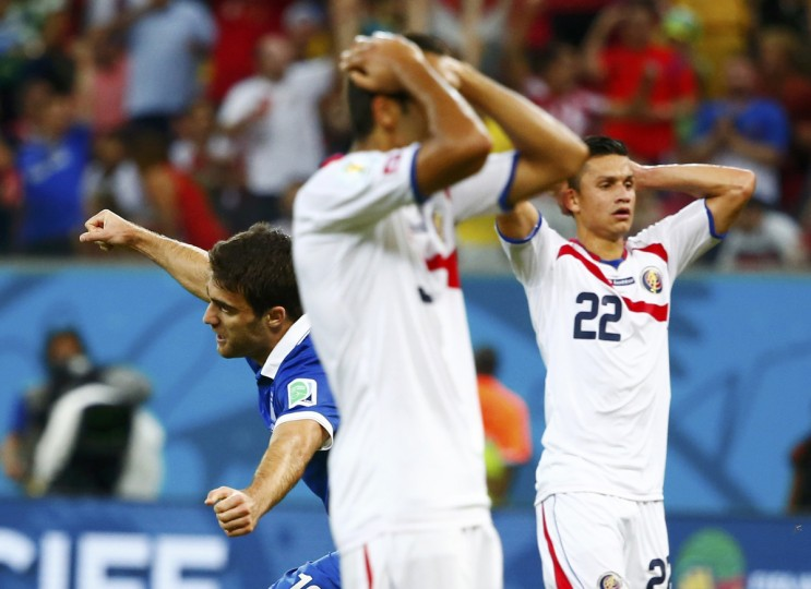 Greece's Sokratis Papastathopoulos (L) celebrates after scoring a goal as Costa Rica's national soccer players react during their 2014 World Cup round of 16 game at the Pernambuco arena in Recife June 29, 2014. (Tony Gentile/Reuters)