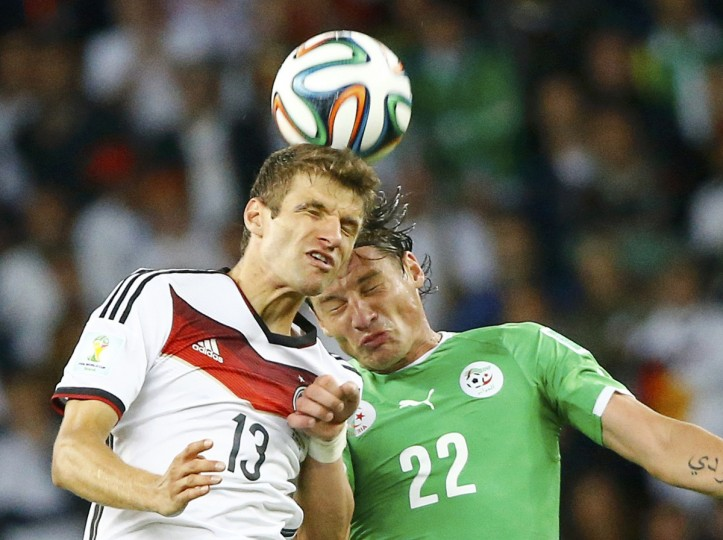 Germany's Thomas Mueller fights for the ball with Algeria's Mehdi Mostefa (R) during their 2014 World Cup round of 16 game at the Beira Rio stadium in Porto Alegre June 30, 2014. (Stefano Rellandini/Reuters)