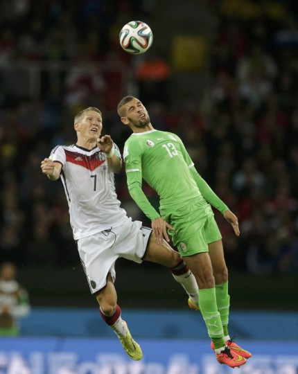 Germany's Bastian Schweinsteiger (L) and Algeria's Islam Slimani jump for the ball during their 2014 World Cup round of 16 game at the Beira Rio stadium in Porto Alegre June 30, 2014. (Henry Romero/Reuters)
