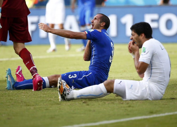 Uruguay's Luis Suarez (R) reacts after clashing with Italy's Giorgio Chiellini during their 2014 World Cup Group D soccer match at the Dunas arena in Natal June 24, 2014. Suarez can learn to stop biting opponents but it will not be a quick or easy process, senior psychologists have said following the Uruguay striker's bite on the shoulder of Italy defender Chiellini at the World Cup. Suarez, twice previously banned for biting, is under investigation by FIFA for the incident late in the Group D clash on Tuesday and faces another lengthy suspension. (Tony Gentile/Reuters)