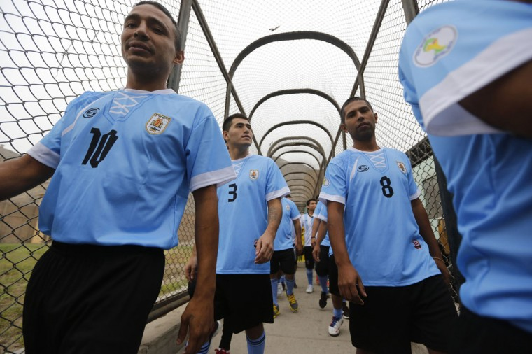 Prisoners, wearing jerseys in the colours of the Uruguay's national soccer team, participate in the opening ceremony of their own version of the 2014 World Cup at the Castro-Castro prison in Lima, June 2, 2014. According to a press release from the prison, about 300 inmates at the Castro-Castro penitentiary are participating in the two-week tournament, which is being held in order to encourage the adoption of sports within the prison population. REUTERS/ Mariana Bazo