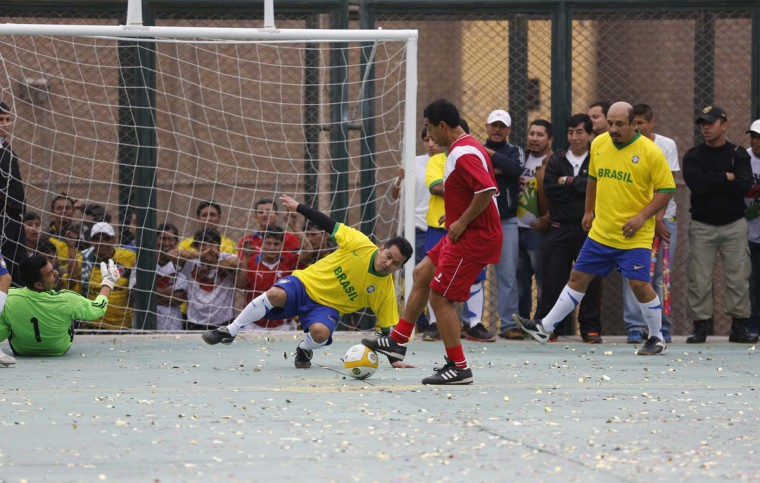 Prisoners, wearing jerseys in the colours of Brazil's national soccer team, play against a team of veteran Peruvian players, who are visitors to the event, at their own version of the 2014 World Cup at the Castro-Castro prison in Lima, June 2, 2014. According to a press release from the prison, about 300 inmates at the Castro-Castro penitentiary are participating in the two-week tournament, which is being held in order to encourage the adoption of sports within the prison population. REUTERS/Mariana Bazo