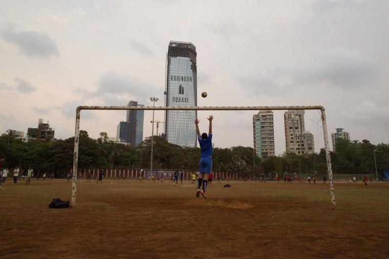 A boy jumps to save a goal while playing soccer at Shivaji Park in Mumbai June 3, 2014. The 2014 Brazil World Cup opens on June 12 and fans around the globe are gearing up for the big tournament. But soccer lovers are not only preparing to watch the world's best professional players battle it out on the pitch; they are also out there kicking a ball about themselves. Reuters photographers on every continent, in countries from China to the Czech Republic, went out to capture images of soccer goalposts used by players to practise the 'beautiful game'. Picture taken June 3, 2014. (Danish Siddiqui/Reuters)