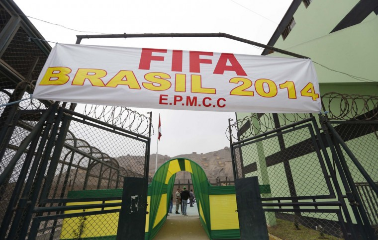 """A banner reading """"Fifa Brazil 2014"""" is displayed as prisoners participate in the opening ceremony of their own version of the 2014 World Cup at the Castro-Castro prison in Lima, June 2, 2014. According to a press release from the prison, about 300 inmates at the Castro-Castro penitentiary are participating in the two-week tournament, which is being held in order to encourage the adoption of sports within the prison population. REUTERS/Mariana Bazo"""