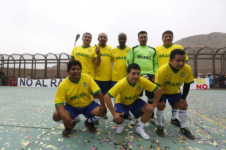 Prisoners, wearing jerseys in the colours of Brazil's national soccer team, participate in the opening ceremony of their own version of the 2014 World Cup at the Castro-Castro prison in Lima, June 2, 2014. According to a press release from the prison, about 300 inmates at the Castro-Castro penitentiary are participating in the two-week tournament, which is being held in order to encourage the adoption of sports within the prison population. REUTERS/Mariana Bazo