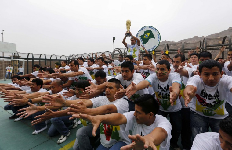 Prisoners participate in the opening ceremony of their own version of the 2014 World Cup at the Castro-Castro prison in Lima, June 2, 2014. According to a press release from the prison, about 300 inmates at the Castro-Castro penitentiary are participating in the two-week tournament, which is being held in order to encourage the adoption of sports within the prison population. REUTERS/Mariana Bazo
